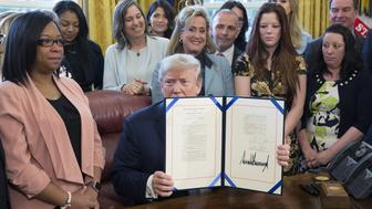 U.S. President Donald Trump holds up a signed sex trafficking bill targeting online platforms at the White House in Washington, D.C., U.S., on Wednesday, April 11, 2018. The legislation would subject online platform operators, such as Facebook or Craigslist, to civil or criminal penalties if they knowingly facilitate sex trafficking. Photographer: Chris Kleponis/Pool via Bloomberg