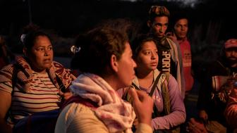 A group of women talk with the medical attention unit of the Refugee Caravan shortly after starting their walk at dusk in Santiago Niltepec