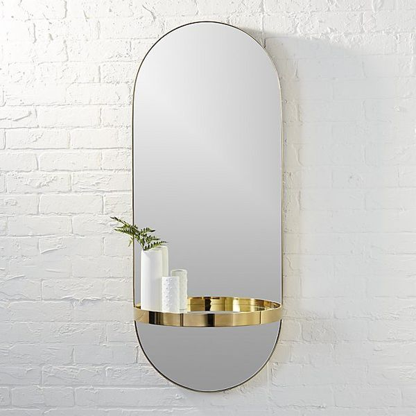 """This <a href=""""https://www.cb2.com/caplet-oval-mirror-with-shelf/s244383"""" target=""""_blank"""">stunning mirror</a> is a conversatio"""