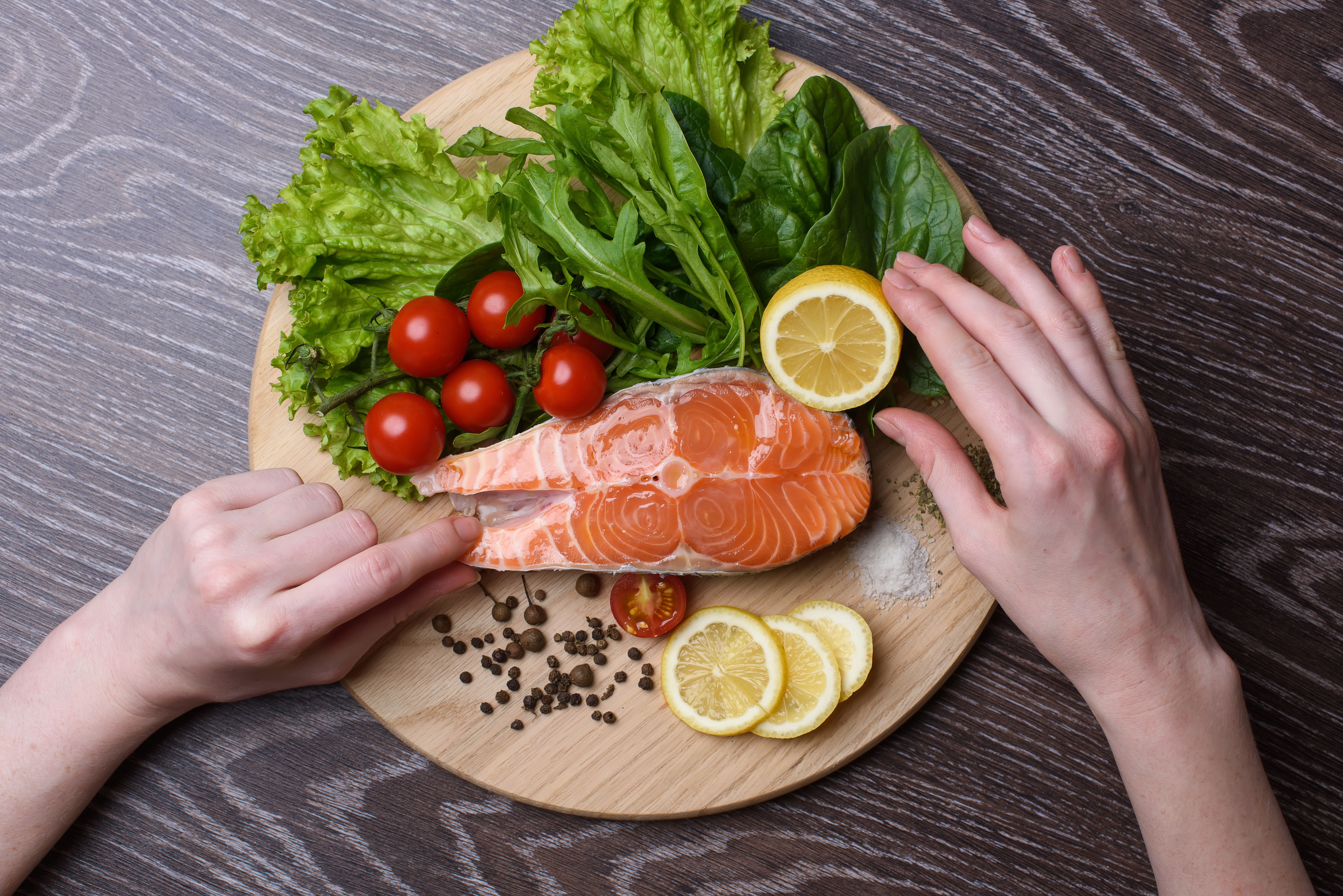 Raw salmon steaks on the wooden board. Lettuce leaves, spices, lemon slices on a wooden board. Woody background. view from above. Hands of a woman in the frame
