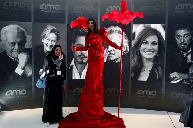 A woman poses at Saudi Arabia's first new commercial movie theater in Riyadh on April 18,