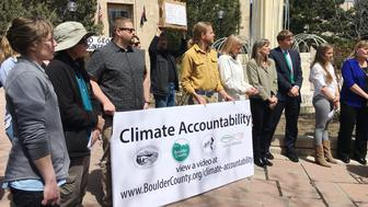 Citizens and supporters hold a banner in front of the Boulder Courthouse