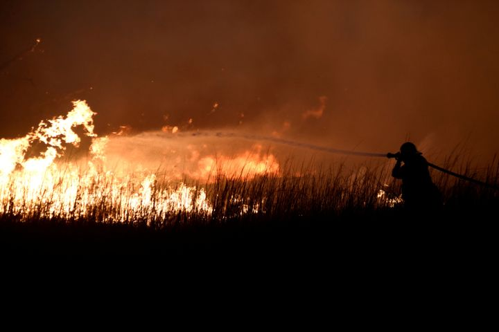 A firefighter works to control the Rhea wildfire near Seiling, Oklahoma, on April 17.