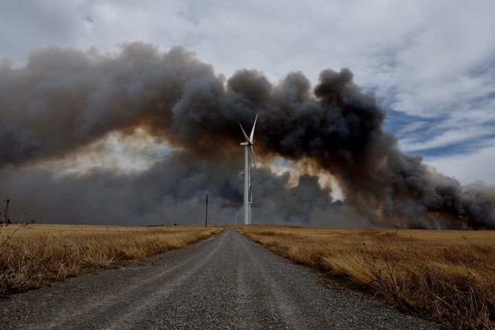 The Rhea fire burns in the distance behind a wind farm near Seiling, Oklahoma.
