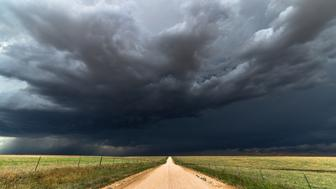 Dark storm clouds sky background with a straight dirt road.