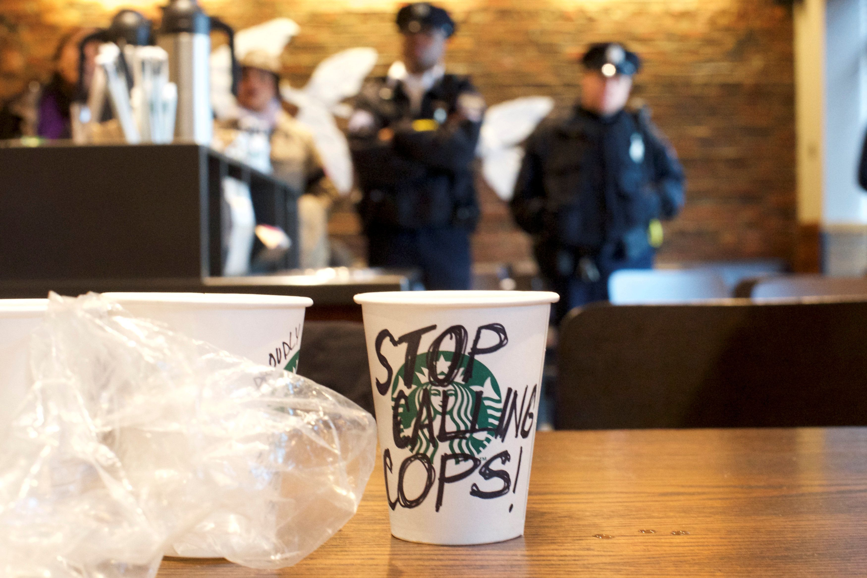 """A Starbucks coffee cup with """"Stop callingcops!"""" written on the side sits on a table as police monitor protesters inside"""
