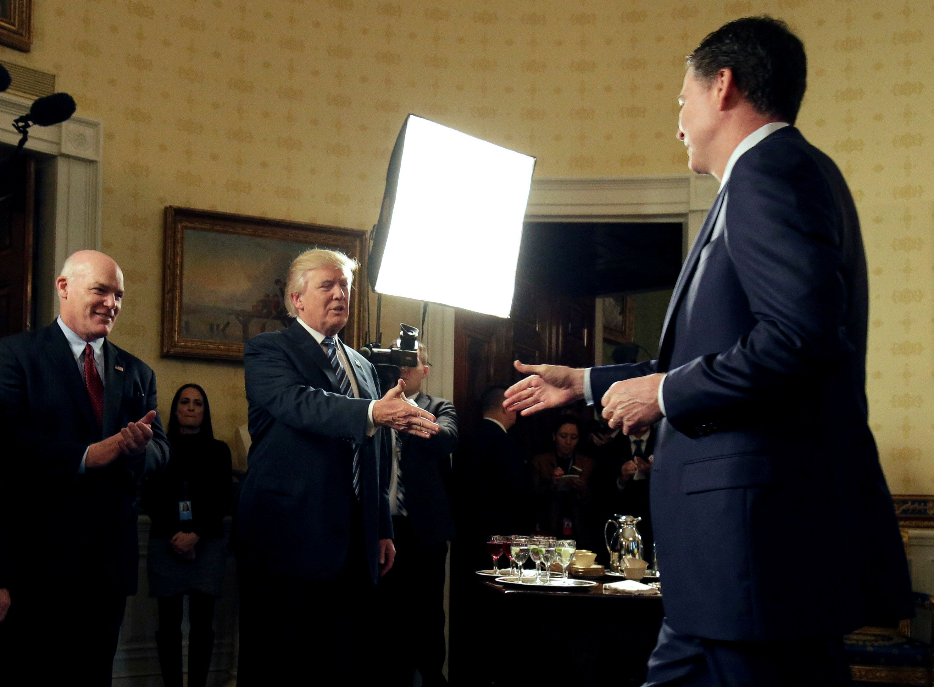 "U.S. President Donald Trump greets Director of the FBI James Comey as Director of the Secret Service Joseph Clancy (L), watches during the Inaugural Law Enforcement Officers and First Responders Reception in the Blue Room of the White House in Washington, U.S., January 22, 2017. Joshua Roberts: ""I have covered the White House for 16 years and normally either the President or the pool is in position when an event starts. In this case the President was not where anyone expected him to be. In fact, he was almost blocking the door when the pool came in. We had to scramble to find a position without bumping him or the furniture as he greeted and thanked members of law enforcement for their security efforts during the inauguration. Luckily, he greeted FBI Director James Comey a few seconds after the pool had made its way into the room."" REUTERS/Joshua Roberts/File Photo  SEARCH ""POY TRUMP"" FOR THIS STORY. SEARCH ""REUTERS POY"" FOR ALL BEST OF 2017 PACKAGES.    TPX IMAGES OF THE DAY"