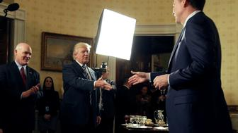 U.S. President Donald Trump greets Director of the FBI James Comey as Director of the Secret Service Joseph Clancy (L) watches during the Inaugural Law Enforcement Officers and First Responders Reception in the Blue Room of the White House in Washington, U.S., January 22, 2017.      REUTERS/Joshua Roberts