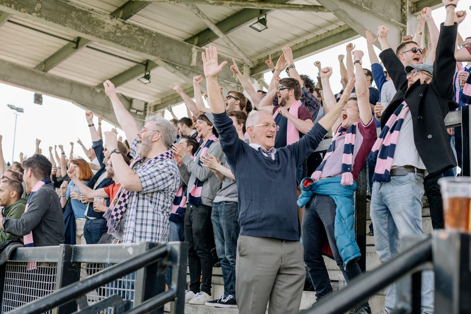 Dulwich Hamlet supporters celebrate a goal against Thurrock F.C. in an April match.