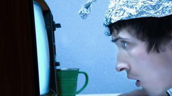 Slightly. A young man wearing a tinfoil hat and watching a fuzzy old TV set. Probably seeing aliens.