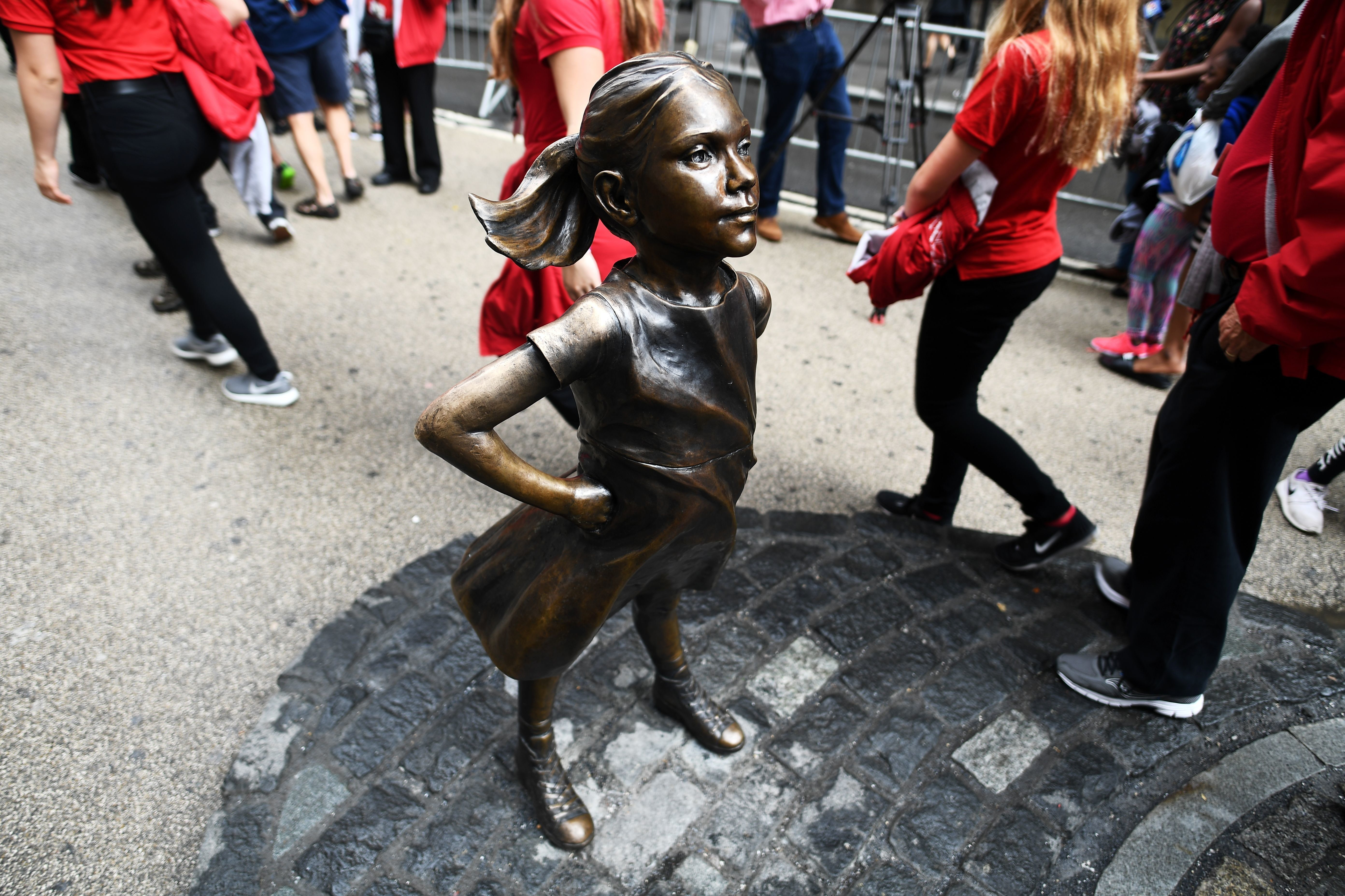 Tourists walk by the Fearless Girl statue in New York City on April 12, 2017.