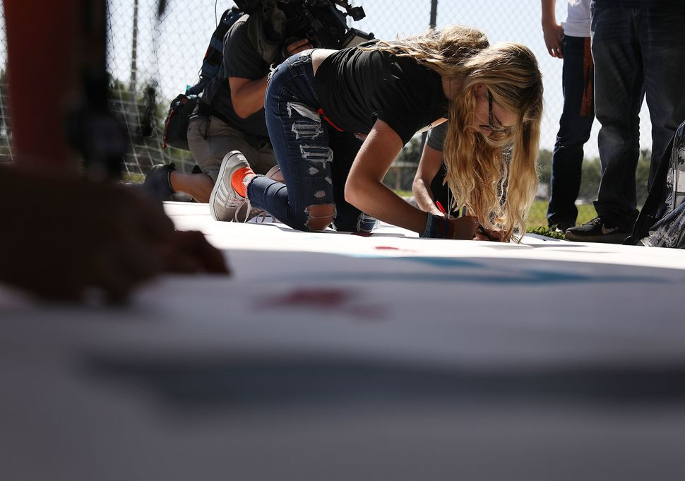 Delany Tarr, a senior, signs a poster as she gathers with some of her classmates from Marjory Stoneman Douglas High Scho