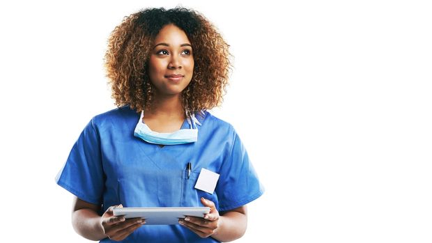Studio shot of an attractive young nurse using a digital tablet against a white background