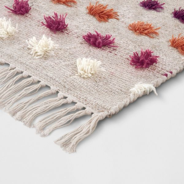 """Get it from <a href=""""https://www.target.com/p/tan-striped-with-poms-woven-fringed-rug-opalhouse-153/-/A-53190743?preselect=53"""