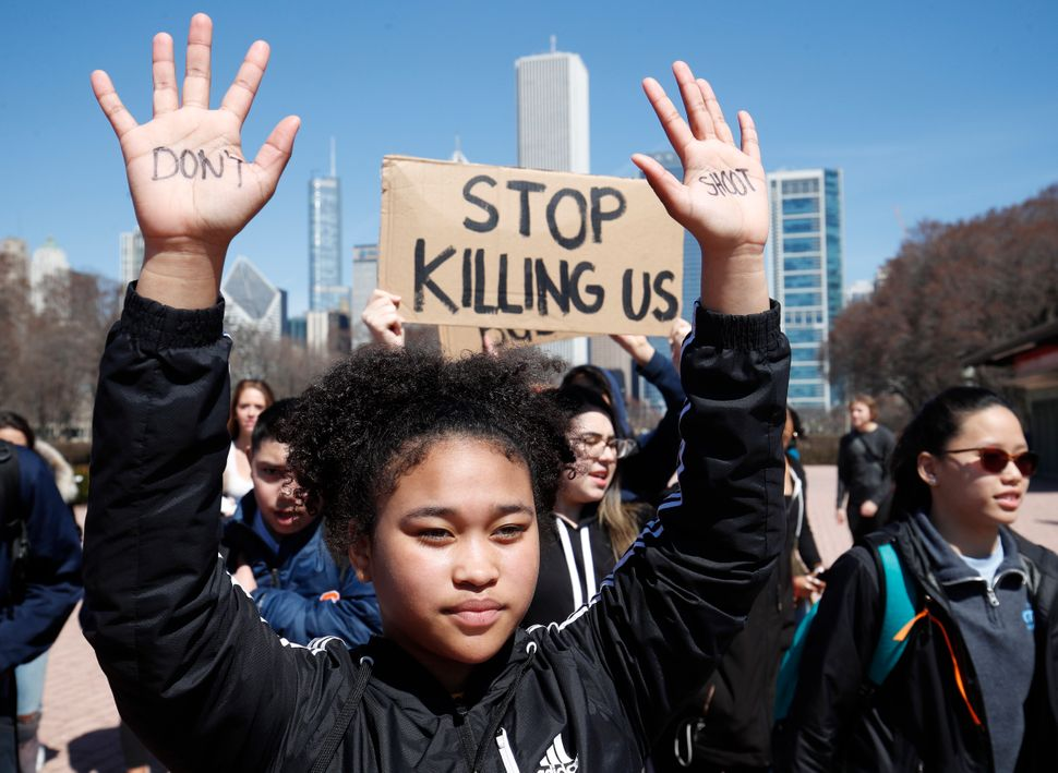 A student holds up her hands while taking part in National School Walkout Day to protest school violence on April 20, 2018 in