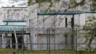 A guard walks between buildings at the Lee Correctional Institution, in Bishopville, South Carolina, on April 16, 2018.  The prison was on lockdown after an overnight riot killed seven while also injuring seventeen others. / AFP PHOTO / Logan Cyrus        (Photo credit should read LOGAN CYRUS/AFP/Getty Images)