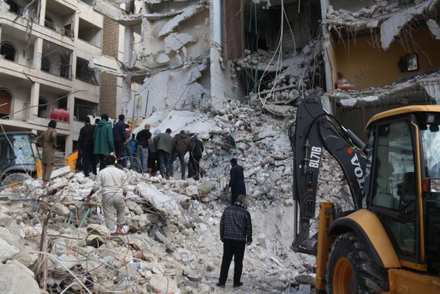 Syrian civil defense members conduct search and rescue operations at the site of the blast that leveled...