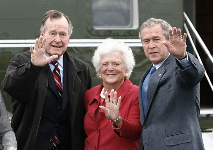 Former President George W. Bush (R) waves alongside his parents, former President George Bush and former first lady Barbara B