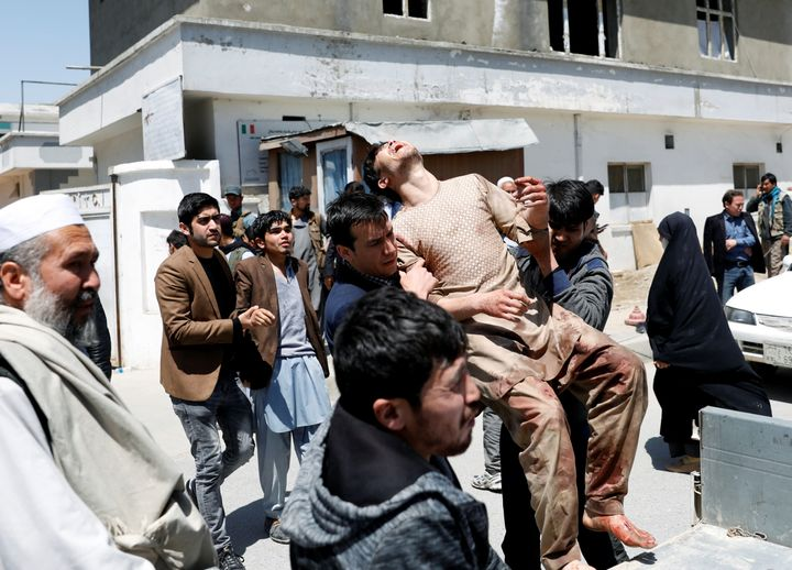 Relatives of victims carry an injured man outside a hospital after a suicide attack in Kabul, Afghanistan, on April 22, 2018.