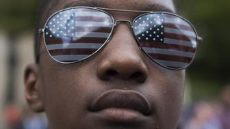 A boy wearing US national flag sunglasses looks on as he takes part in the march for Racial Justice in Washington, DC, on September 30, 2017.  / AFP PHOTO / Andrew CABALLERO-REYNOLDS        (Photo credit should read ANDREW CABALLERO-REYNOLDS/AFP/Getty Images)