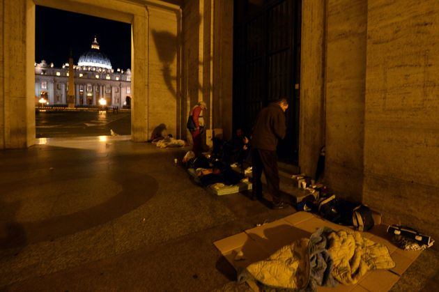 Homeless persons prepare to sleep under an arcade at the Vatican in November