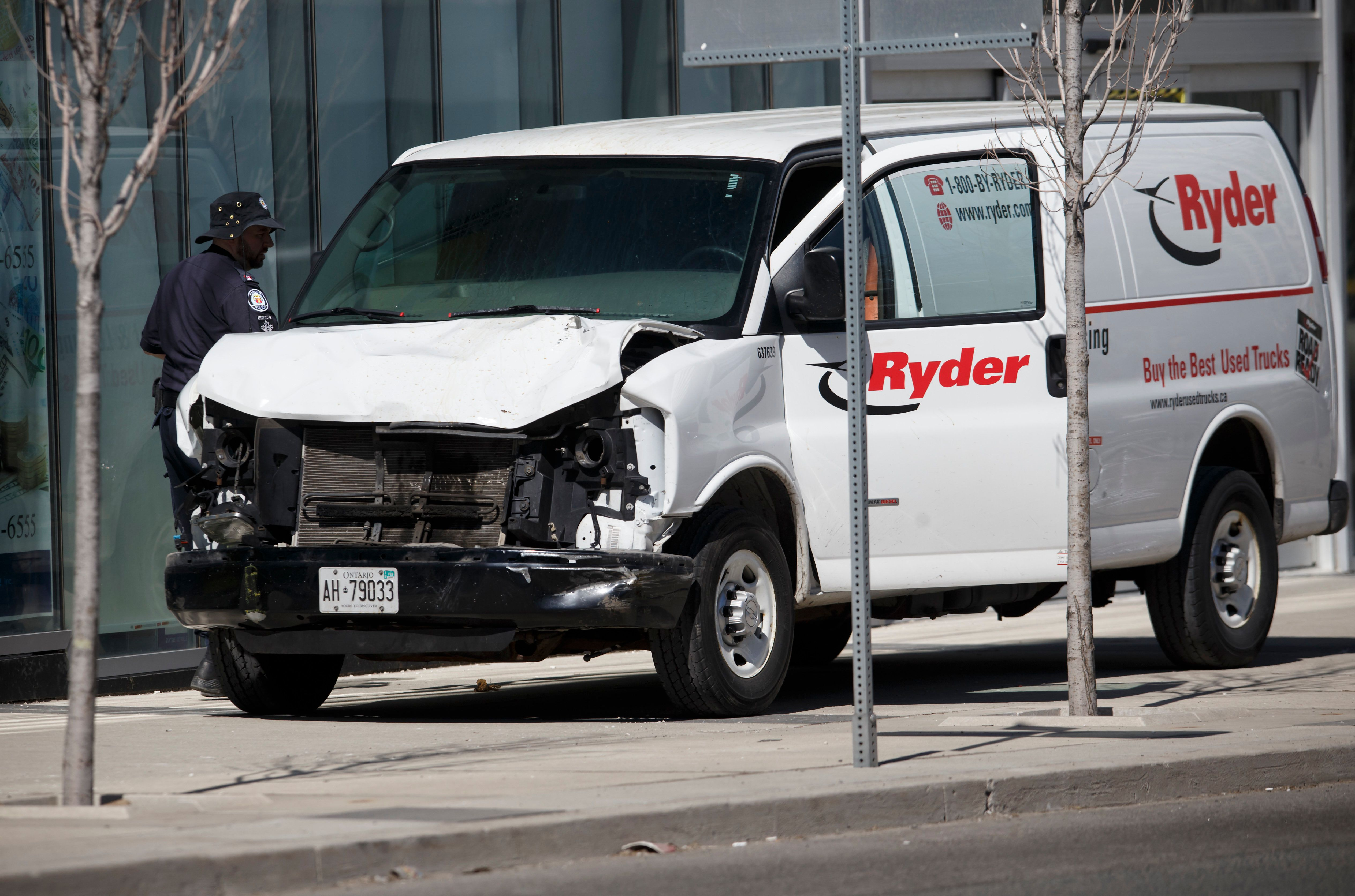 Police inspect a van suspected of being involved in a collision injuring at least eight people at Yonge Street and Finch Aven