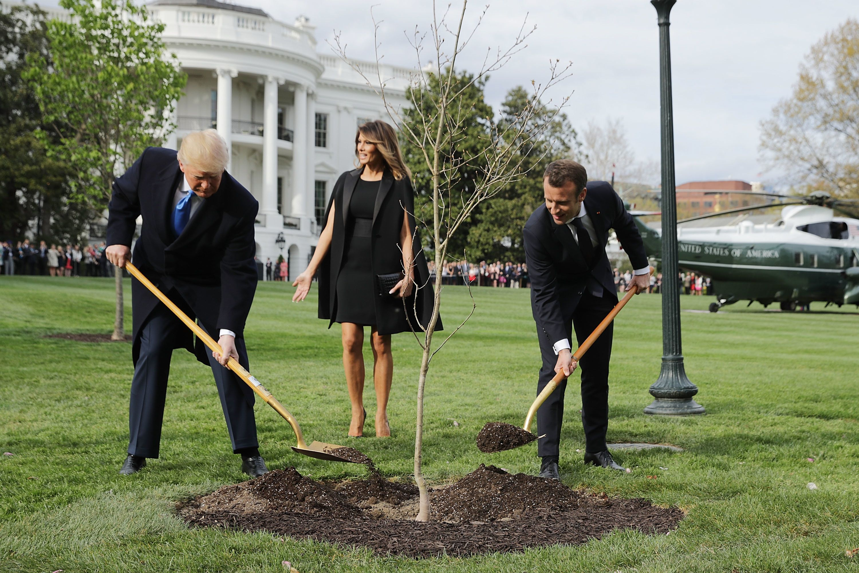 WASHINGTON, DC - APRIL 23:  (L-R) U.S President Donald Trump, U.S. first lady Melania Trump and French President Emmanuel Macron participate in a tree-planting ceremony on the South Lawn of the White House April 23, 2018 in Washington, DC. The European Sessile Oak is a gift from the Macrons and comes from Belleau Woods, where more than 9,000 American marines died during battle in June 1918 during the First World War. According to the first lady's office 'The forest is a memorial site and important symbol of the sacrifice the United States made to ensure peace and stability in Europe.' (Photo by Chip Somodevilla/Getty Images)