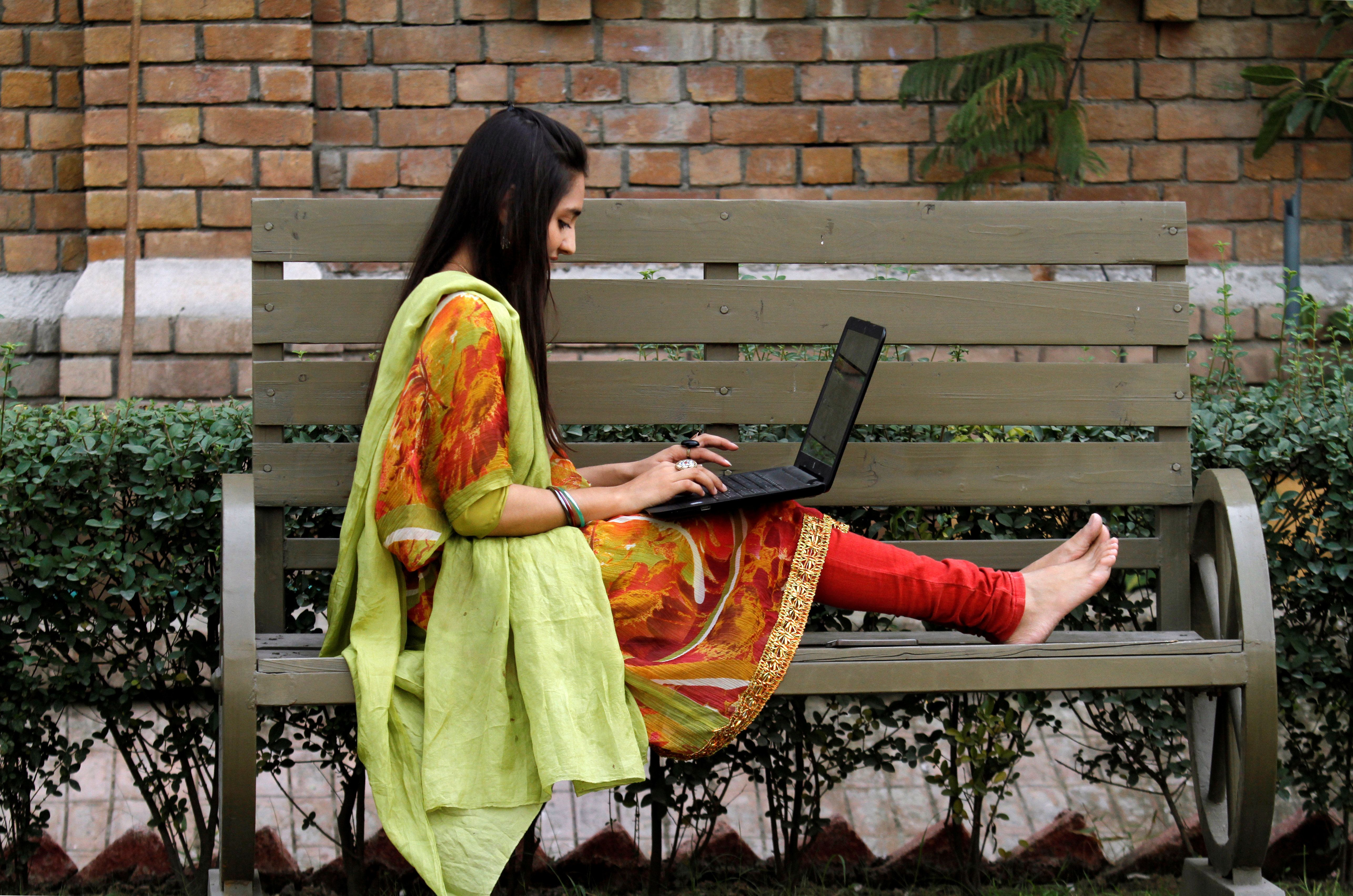 A student works on her computer sitting on a bench at Shaheed Benazir Bhutto Women's University in Peshawar, Pakistan October 19, 2017  REUTERS/ Fayaz  Aziz