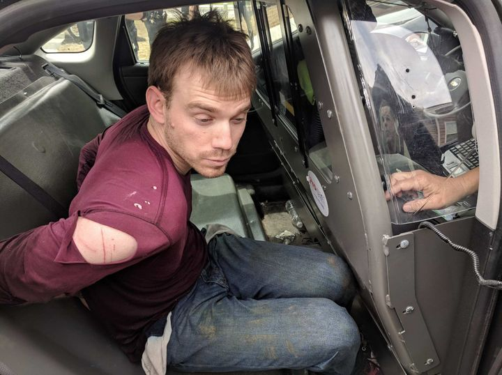 In this handout provided by the Metro Nashville Police Department, Travis Reinking, 29, is placed in the back of a police car