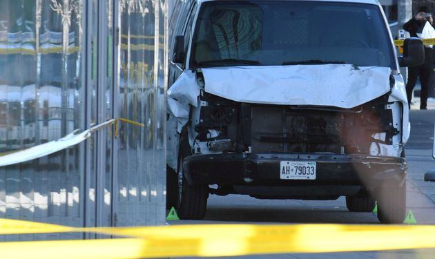 A damaged van is seized by police after it struck about two dozen people Tuesday at a major intersection...