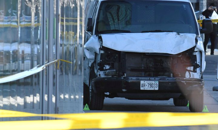 A damaged van is seized by police after it struck about two dozen people Tuesday at a major intersection in Toronto.
