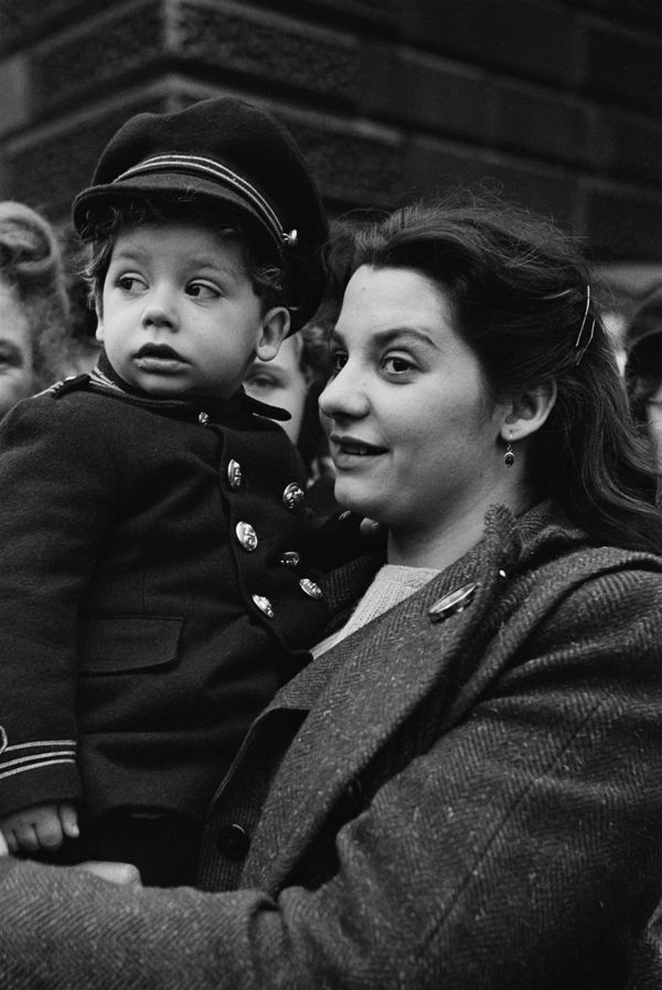A woman holds up a toddler to watch the royal procession in Londonfor the wedding.