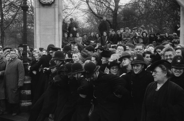 Police hold back crowds outside Buckingham Palace in London during the wedding.
