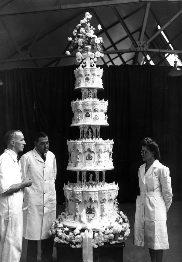 """Confectioners stand next to the impressive official cake, which stood<a href=""""https://www.royal.uk/70-facts-about-queen"""