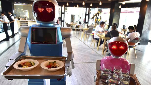 Robot couple Xiaolan (L) and Xiaotao carry trays of food at a restaurant in Jinhua, Zhejiang province, China, May 18, 2015. The restaurant, which opened on Monday has two robots delivering food for customers. The robots were designed as a couple, Xiaolan and Xiaotao, according to local media. REUTERS/Stringer CHINA OUT. NO COMMERCIAL OR EDITORIAL SALES IN CHINA