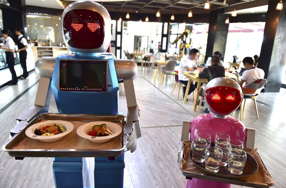 Robots known as Xiaolan (L) and Xiaotao serve customers at a restaurant in Jinhua, Zhejiang province, China.