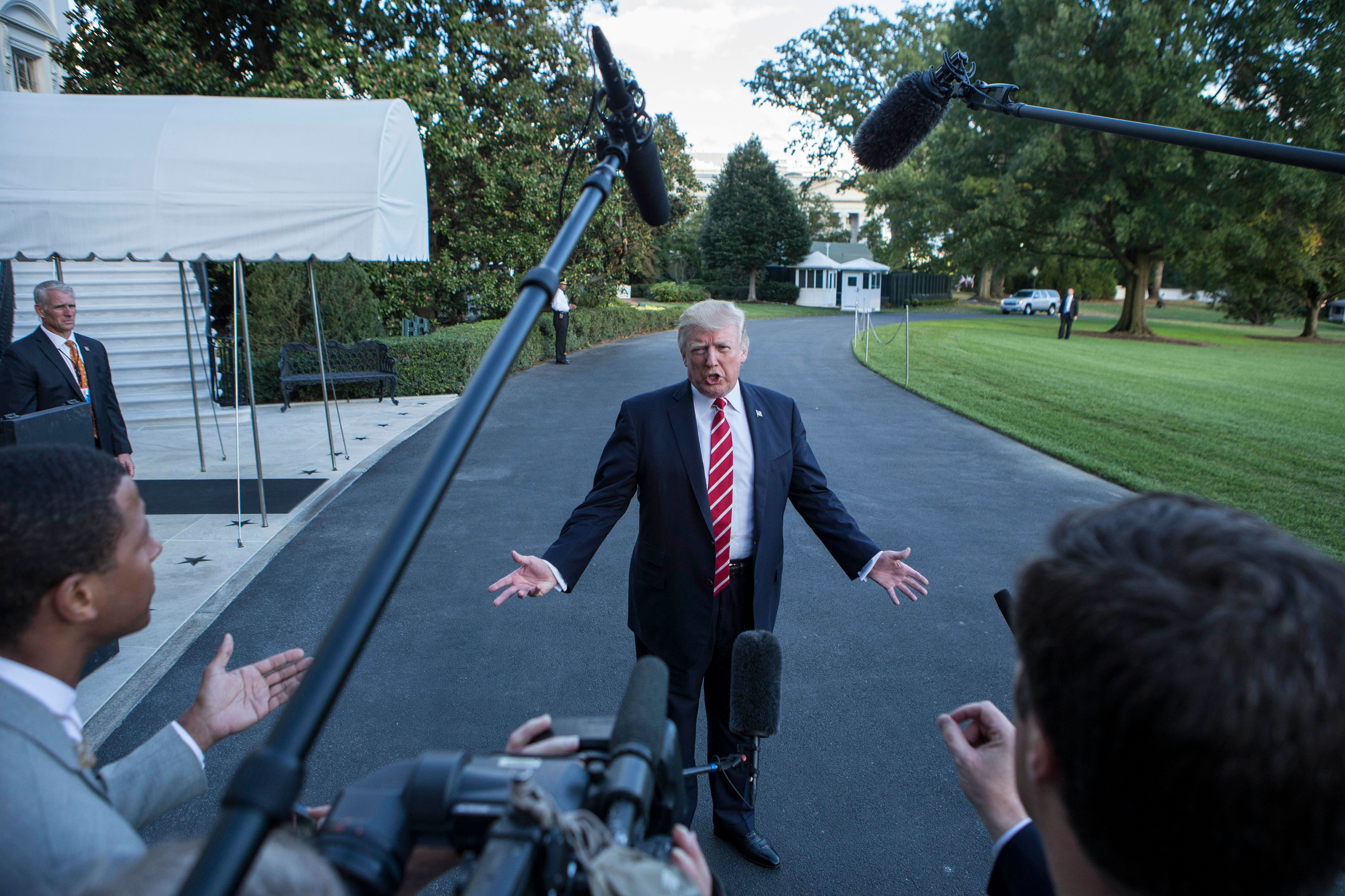 US President Donald Trump speaks with reporters outside the White House prior to his departure aboard Marine One on October 7, 2017.  During the exchange, President Trump called NBC News, 'Fake News' after the news agency reported tension between Trump and US Secretary of State Rex Rex Tillerson. The President will travel to Greensboro, North Carolina this evening to participate in a roundtable discussion with Republican National Committee members. / AFP PHOTO / Alex EDELMAN        (Photo credit should read ALEX EDELMAN/AFP/Getty Images)
