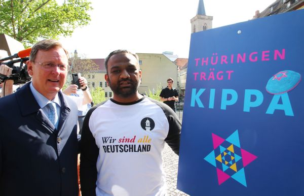 Thuringia's State Premier Bodo Ramelow (L) and Mailk Mohamed Suleman from the Muslim Ahmadiyya community pose for a picture d
