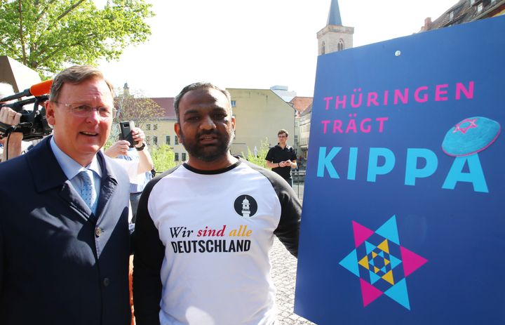 German politician Bodo Ramelow (L) and Mailk Mohamed Suleman from the Muslim Ahmadiyya community pose next to an ad for the '