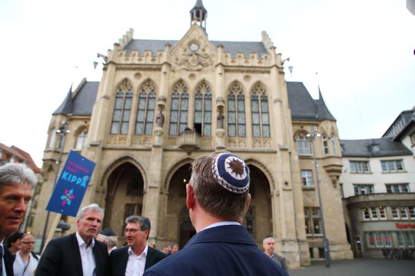 Thuringia's State Premier Bodo Ramelow (C) wears a kippa during the rally.