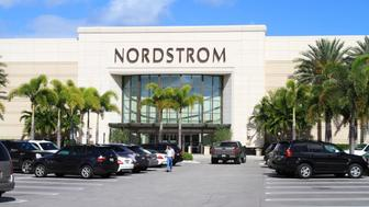 'West Palm Beach, USA - March 13, 2012: This is a view of a  Nordstrom retail store at a  shopping mall in South Florida. A busy parking lot is filled with cars and a pedestrian is walking away from the store. Nordstrom offers apparel, shoes, jewelry, cosmetics and accessories for women, men and kids. They carry most of the popular designer brands.'