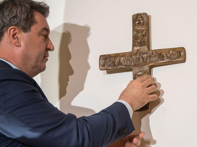 Bayerns Ministerpräsident hängt das erste Kreuz selbst auf – hier in der bayerischen Staatskanzlei.