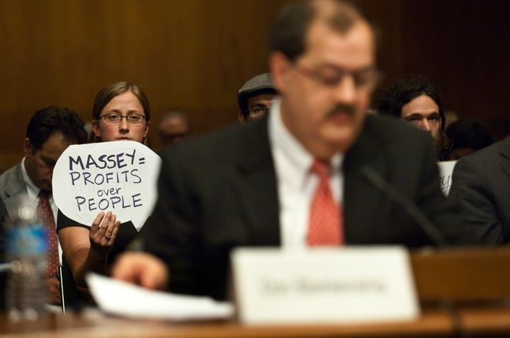 A protester holds a sign behind Don Blankenship, who had been chairman and CEO of Massey Energy Co. until a deadly explosion