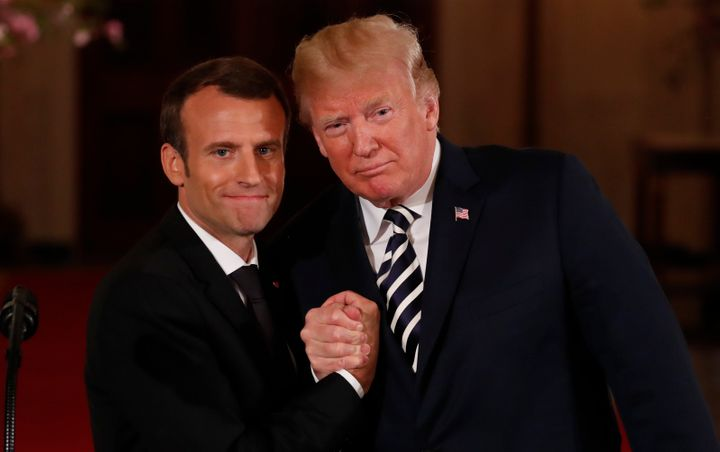 French President Emmanuel Macron clasps hands with U.S. President Donald Trump after their joint news conference at the White