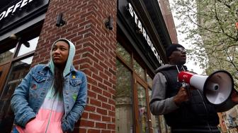 Asa Khalif (right), of BLM Philly,  stands outside as protesters gather at the Starbucks location in Center City Philadelphia, PA on April 15, 2018 where days earlier two black men were arrested. The arrest prompted controversy after video of the incident became viral. (Photo by Bastiaan Slabbers/NurPhoto via Getty Images)