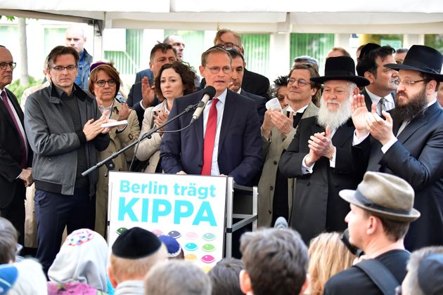 Berlin's mayor Michael Mueller (C) speaks during the