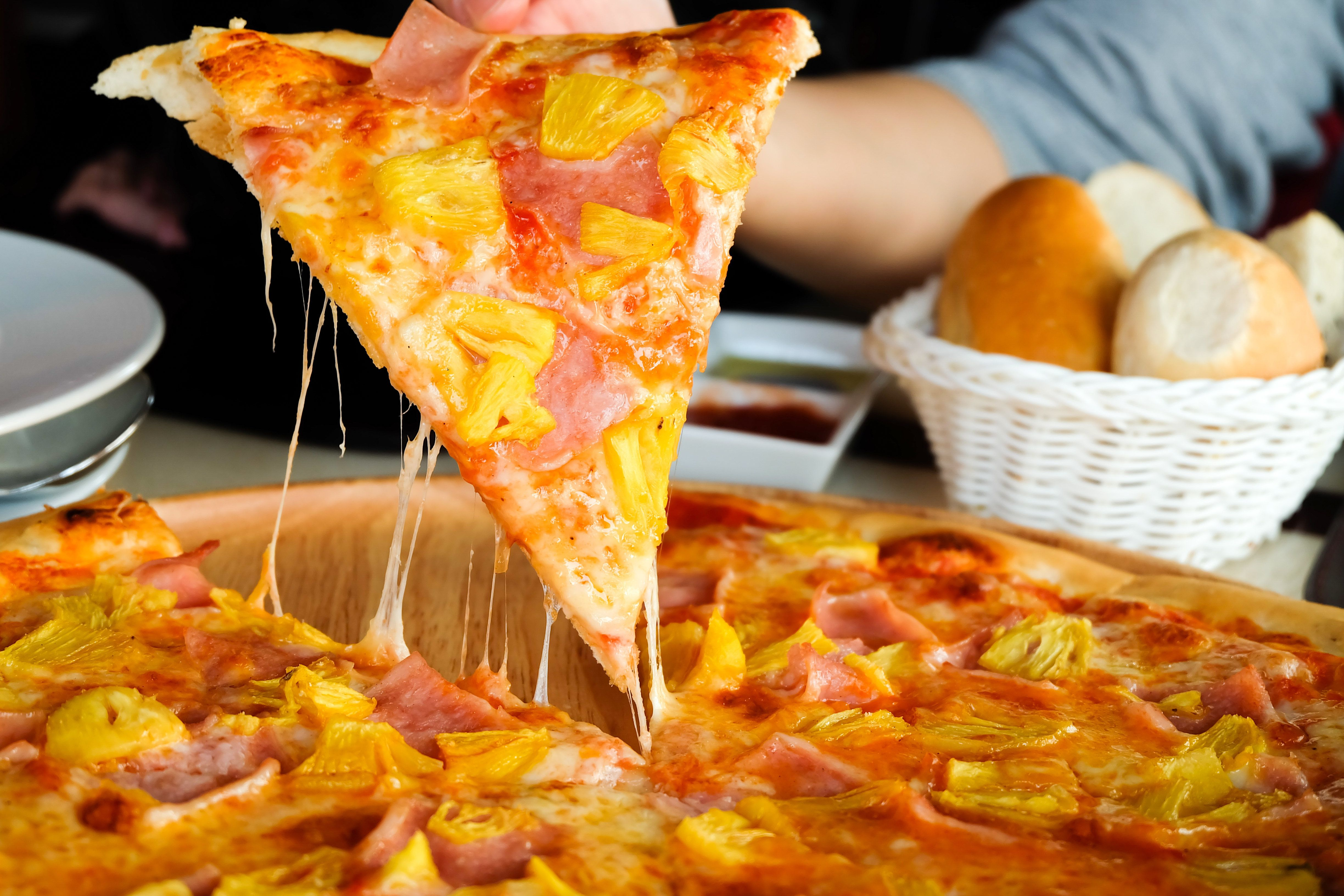 Close up Woman's hand picked Hawaiian pizza from a wooden tray on the table.