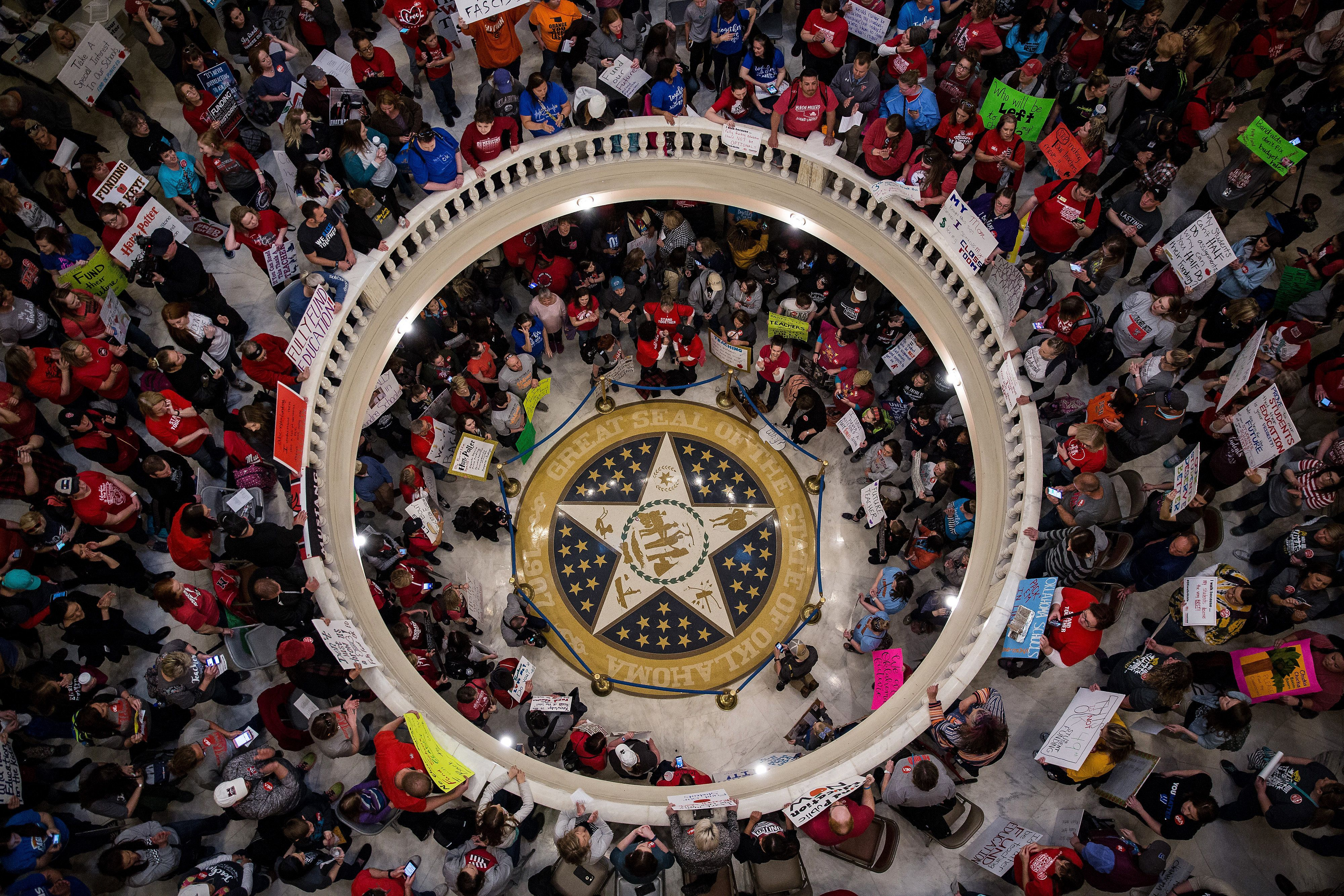 Teachers and demonstrators hold signs during a rally inside the Oklahoma State Capitol building in Oklahoma City, Oklahoma, U.S., on Tuesday, April 3, 2018. Hundreds of teachers crowded into the Oklahoma Capitol for a second day Tuesday to press demands for additional funding for the state's public schools. Photographer: Scott Heins/Bloomberg via Getty Images