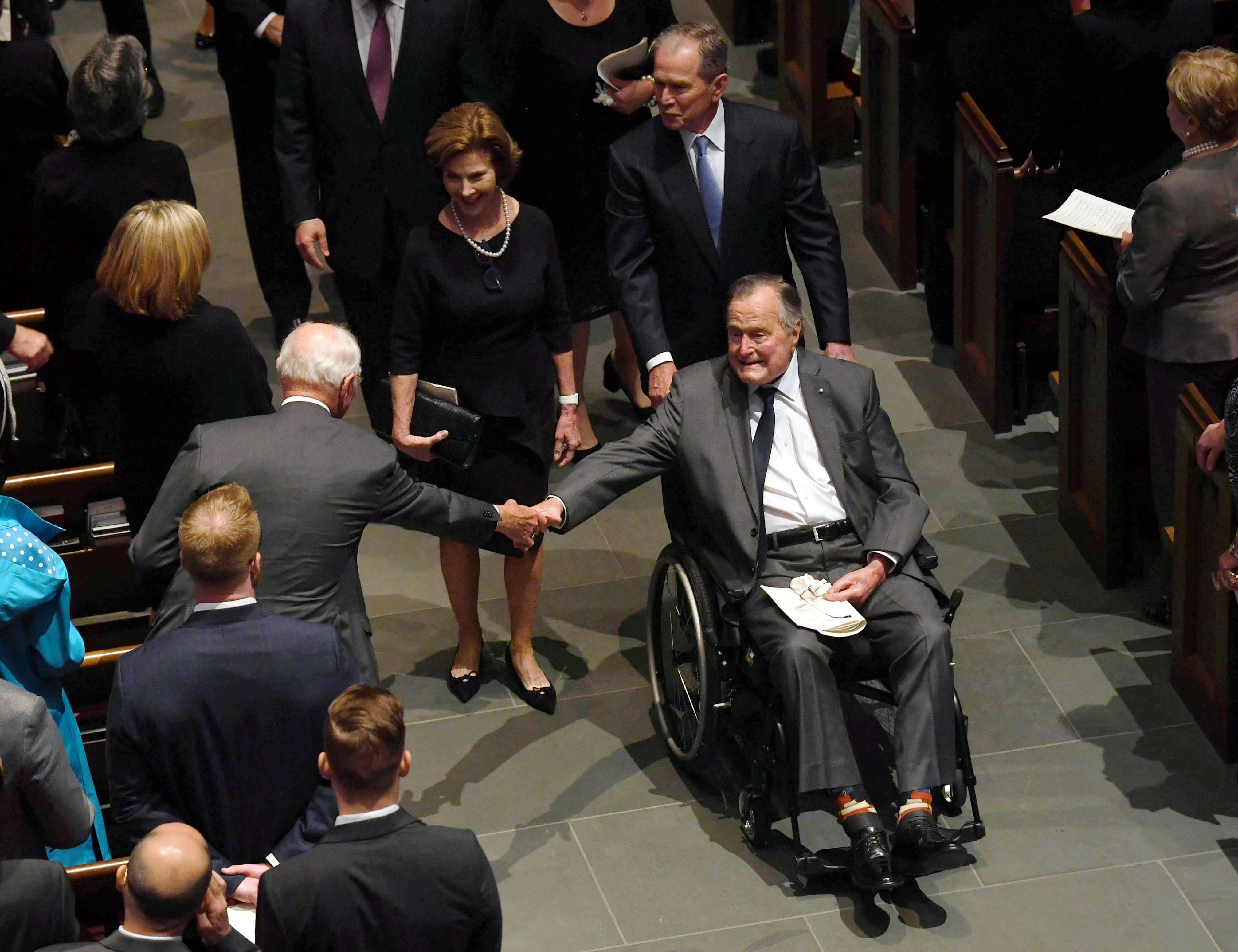 Former President George H.W. Bush is greeted as he exits the funeral services of his wife Barbara Bush, followed by his daughter-in-law former First Lady Laura Bush and son, former President George W. Bush at St. Martin's Episcopal Church in Houston, Texas, U.S., April 21, 2018.  Jack Gruber/Pool via Reuters