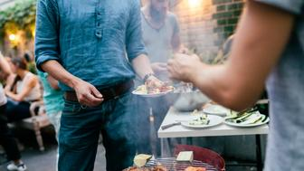 A group of friends are serving each other fresh food, straight from the barbecue at a  summer evening get together.